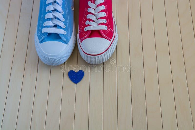 Lieben Sie Hintergrund mit zwei verschiedenen Turnschuhen und blauem Herzen stockbilder