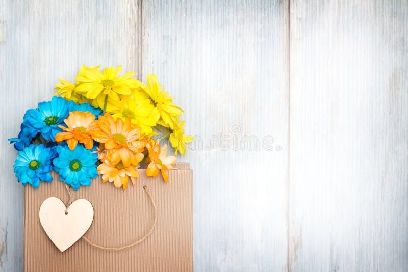 Lieben Sie kaufenden abstrakten Hintergrund mit Papiertüte- und Frühlingsblumen stockfotografie