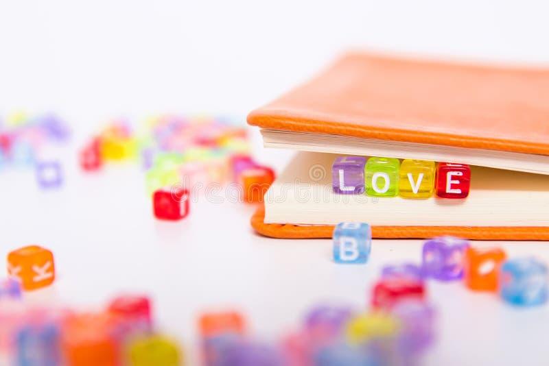 LIEBEN Sie Wort auf buntem Perlenblock als Bookmark im Buch Liebe und romantische Erfindung, glückliche Valentinstaggrußkarte und lizenzfreie stockbilder