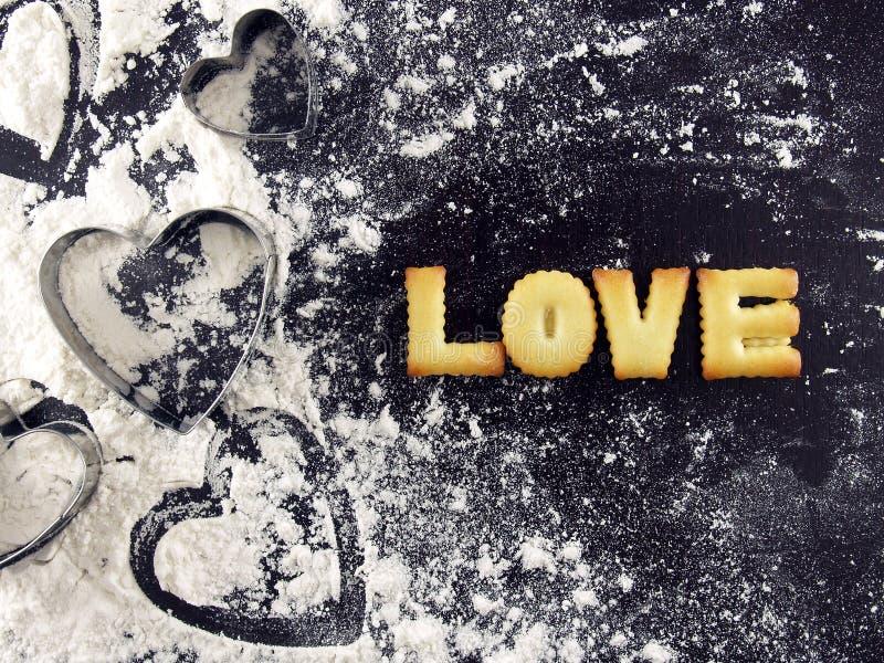 Lieben Sie Wort, Keksplätzchenbuchstaben mit Herz geformtem Plätzchenschneider und Mehl lizenzfreie stockbilder