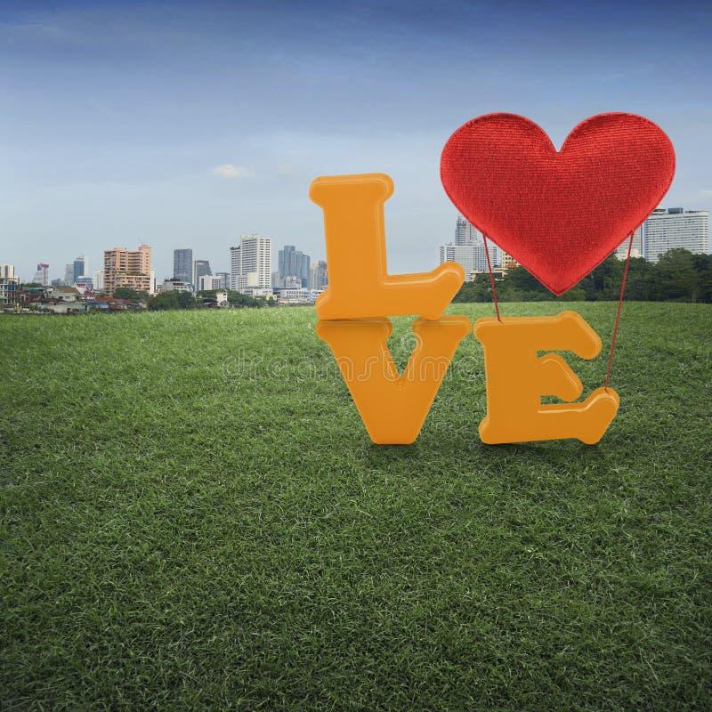 Lieben Sie Wort mit Herzform Ballon auf grüner Rasenfläche und offic stockbilder