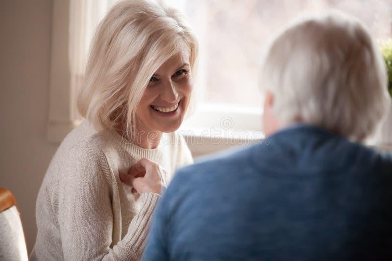 Liebende ältere Paare, die zu Hause sprechen und lachen lizenzfreie stockfotos