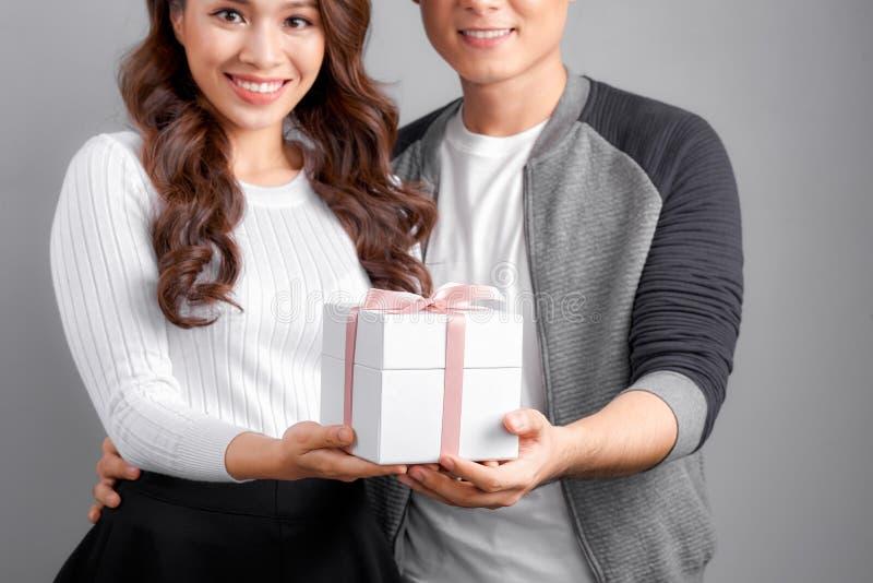 Liebende asiatische Paare, die eine Geschenkbox, Fokus auf Händen zusammenhalten stockfotografie