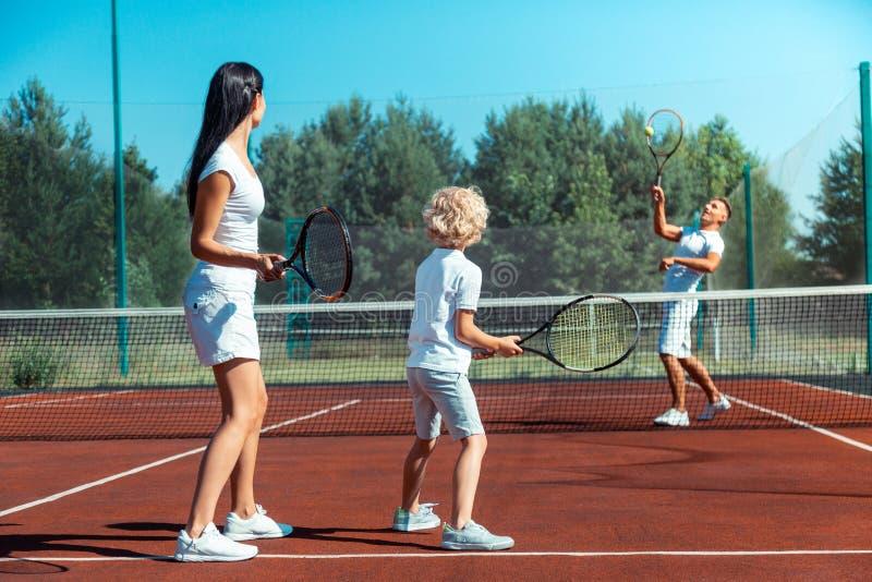 Liebende Eltern, die Tennis mit ihrem netten blond-haarigen Sohn spielen lizenzfreie stockbilder