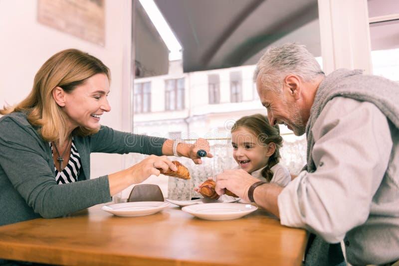 Liebende interessierende Großeltern, die ihrem kleinen Mädchen frisches Hörnchen geben stockfotos
