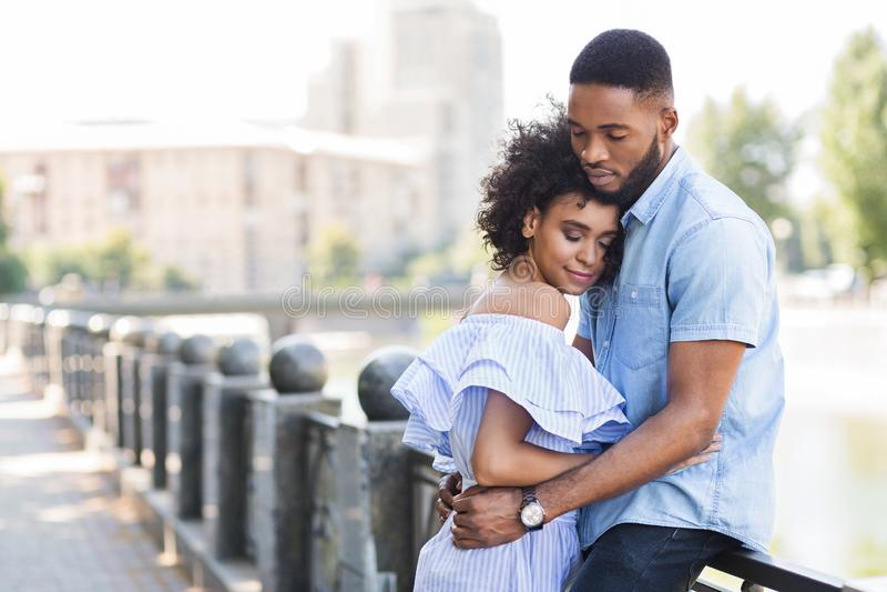 Liebende junge Paare, die draußen zarten Moment genießen stockbild