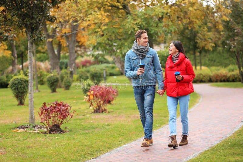 Liebende junge Paare mit Kaffee auf romantischem Datum im Herbstpark stockfoto