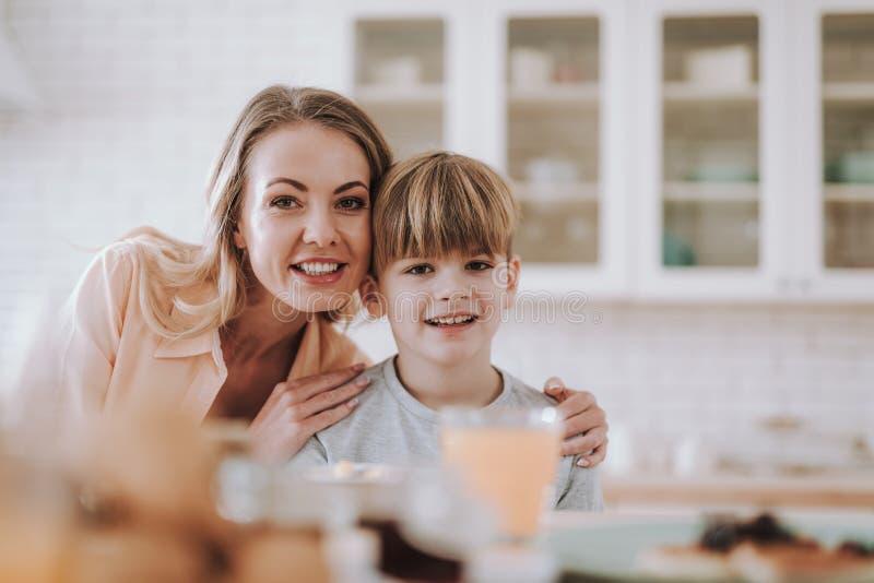 Liebende Mutter, die ihren Sohn umarmt und zur Kamera l?chelt lizenzfreie stockfotos