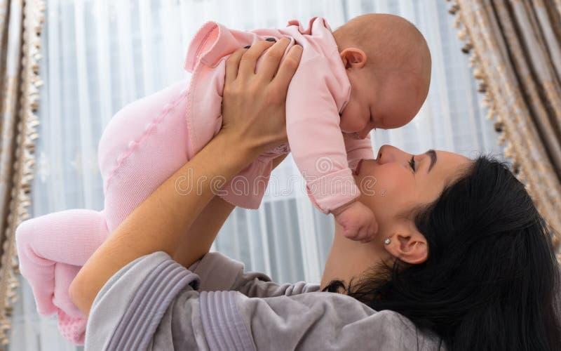 Liebende Mutter, die mit ihrem kleinen Baby spielt lizenzfreies stockfoto