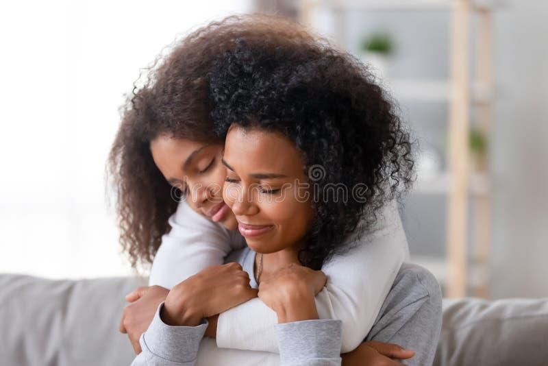 Liebende Mutter und Tochter mit der geschlossenen Augenumfassung lizenzfreie stockbilder