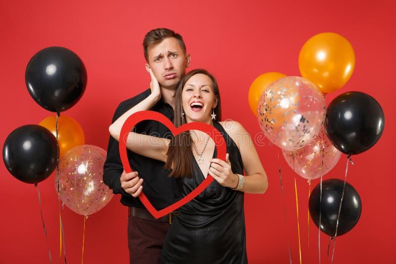 Liebende Paare in der schwarzen Kleidung halten das Herz, das Geburtstagsurlaubsparty auf heller roter Hintergrundluft feiert stockfotos