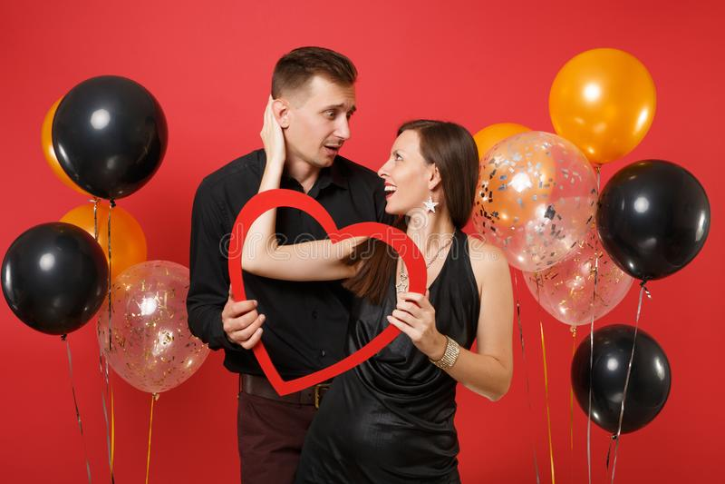 Liebende Paare in der schwarzen Kleidung halten das Herz, das Geburtstagsurlaubsparty auf heller roter Hintergrundluft feiert stockbild