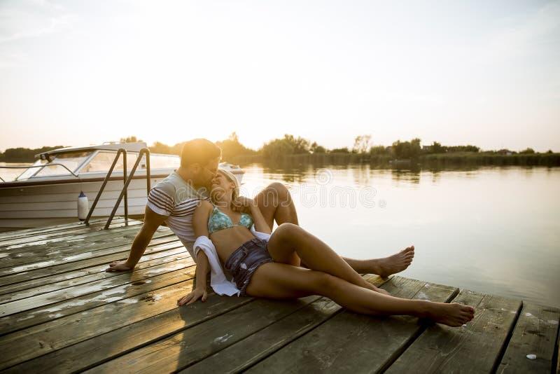 Liebende Paare, die auf dem Pier auf See sitzen stockfotografie