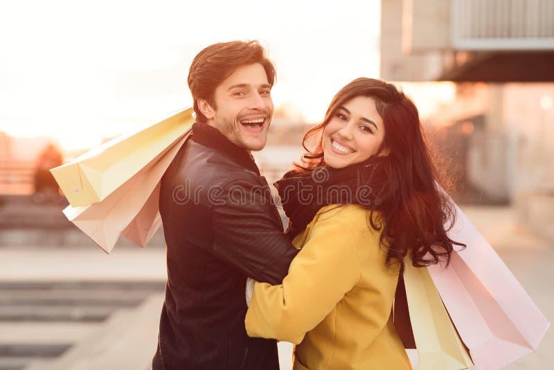 Liebende tragende Einkaufstaschen der Paare und Gehen bei Sonnenuntergang lizenzfreie stockbilder