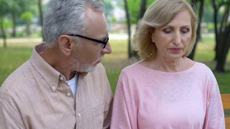Liebender gealterter Ehemann, der trauriges Fraufreien, männliche Entschuldigung, Beziehungskrise stützt stockbild