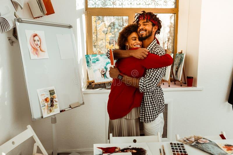 Liebender hübscher bärtiger Mann, der seine schöne Freundin umarmt stockbild