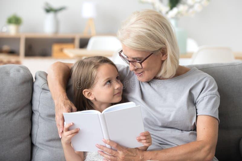 Liebendes Enkelin-Lesebuch der Großmutter unterrichtendes, das O sitzt lizenzfreies stockfoto