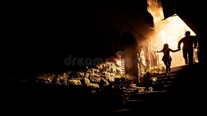 Liebendes romantisches Bild des Paarhändchenhaltens, welches oben die Treppe laufen lässt stockfotografie