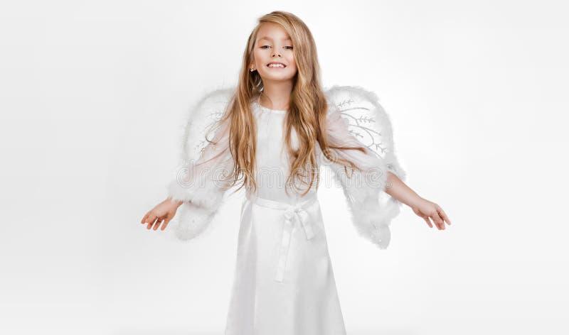 Liebenswürdiges kleines Mädchen, Blondine, kleine Prinzessin, die in einer Engelsausstattung gekleidet wird, besteht Griffgebet i stockfotografie