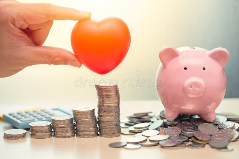 Liebes-Herz und Rettungsgeld-Sparschwein für Lebensversicherung stockfotografie