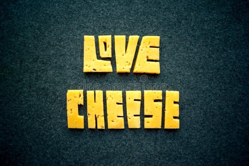 Liebes-Käsetextwort auf dunklem Hintergrund Schnitzen Sie gelben Cheddarkäse I stockfoto