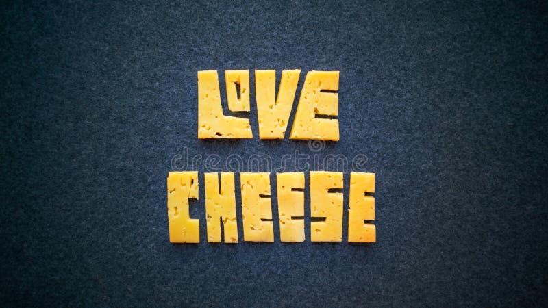 Liebes-Käsetextwort auf dunklem Hintergrund Schnitzen Sie gelben Cheddarkäse I lizenzfreies stockfoto