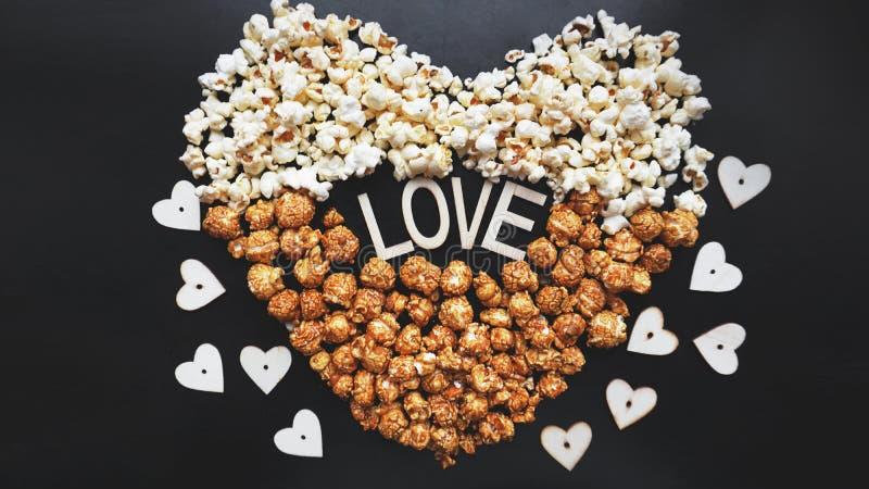 Liebes-Kinokonzept des Popcorns vereinbart in einer Herzform Sortiertes Popcorn lizenzfreies stockbild