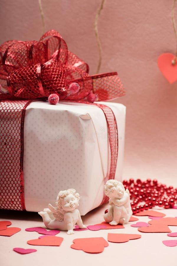 Liebes- und Feiertagskonzept: eingewickeltes Geschenk und Amoren unter Herzen lizenzfreie stockfotografie