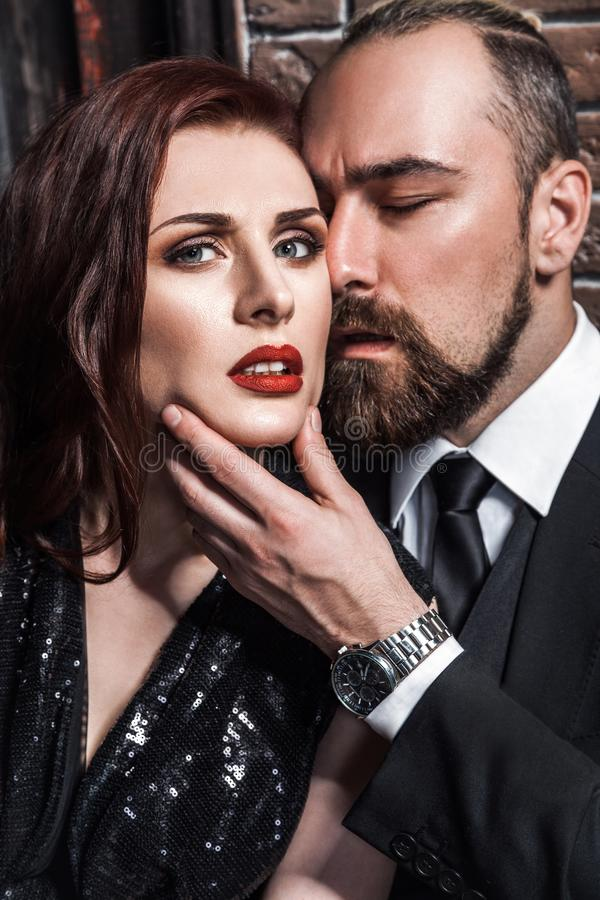 Liebes- und Leidenschaftskonzept, Nahaufnahme Loking an der Kamera Bärtiger Mann, der sinnliche Frau der Rothaarigen küsst stockfotografie