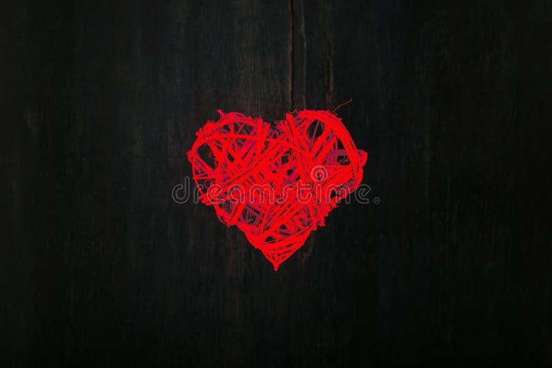 Liebes-Valentinsgruß-rotes Herz geformter Kranz auf dunklem Hintergrund stockbild