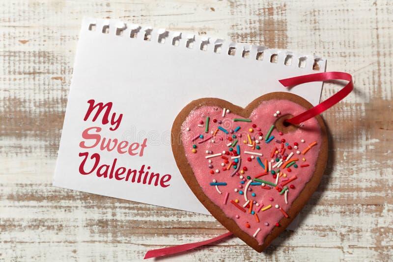 Liebesbrief auf Papier- und Plätzchenherzen mit rotem Band auf hölzernem rustikalem Schreibtisch stockfotos