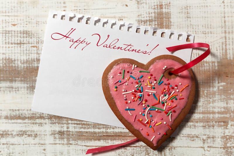 Liebesbrief auf Papier- und Plätzchenherzen mit rotem Band auf hölzernem rustikalem Schreibtisch lizenzfreie stockbilder