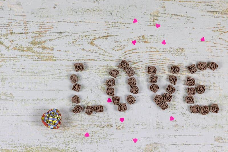 Liebesbriefe von den braunen Rosen auf einem hölzernen Hintergrund, Draufsicht Rote kleine Herzen gemacht vom Papier auf hölzerne lizenzfreie stockbilder