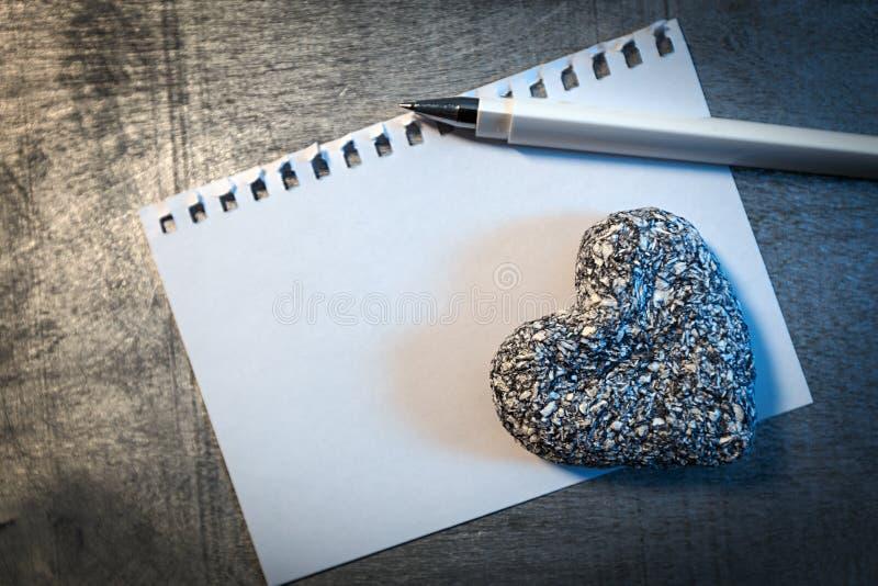 Liebesbriefschablone auf Papier mit Stift- und Steinherzen auf hölzernem rustikalem Schreibtisch, lizenzfreies stockbild