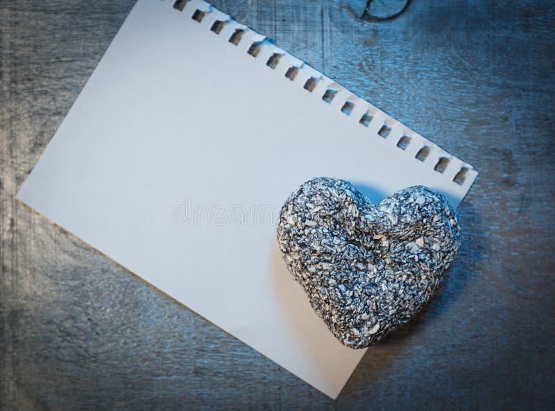Liebesbriefschablone auf Papier- und Steinherzen auf hölzernem rustikalem Schreibtisch, lizenzfreie stockbilder