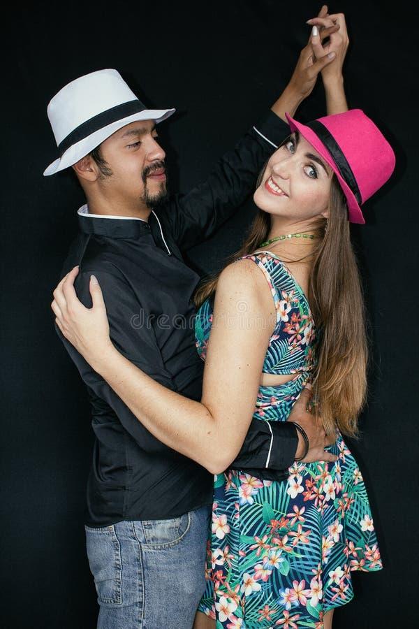 Liebesgeschichte, Mann und Frau Brunette in den Hüten, die auf einen schwarzen Hintergrund tanzen lizenzfreies stockfoto
