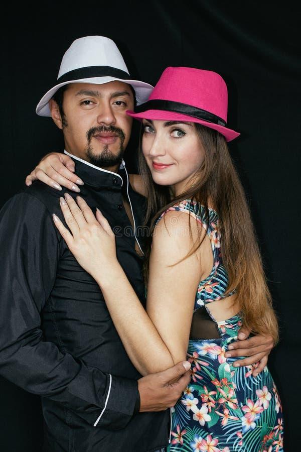 Liebesgeschichte, Mann und Frau Brunette in den Hüten, umarmend auf einem schwarzen Hintergrund lizenzfreie stockfotografie