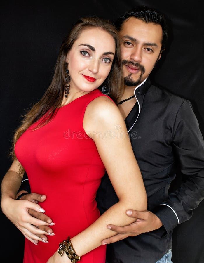 Liebesgeschichte, Mann und Frau Brunettes, die auf einem schwarzen Hintergrund umarmen stockfotografie