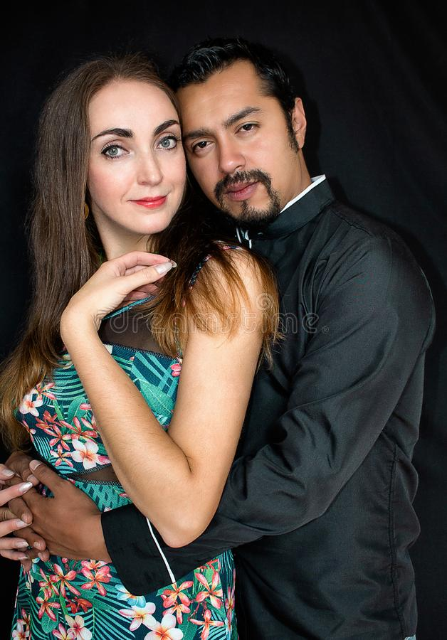 Liebesgeschichte, Mann und Frau Brunettes, die auf einem schwarzen Hintergrund umarmen stockfotos