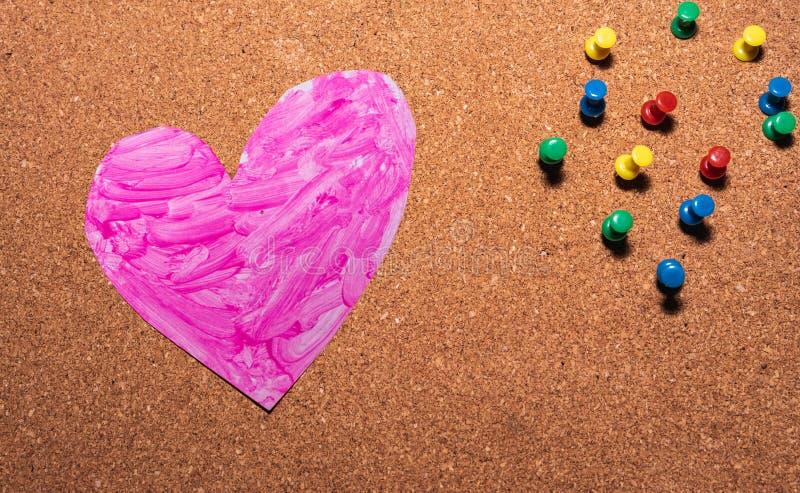 Liebesherzsymbol malte rosa auf einem Korkenbrett lizenzfreies stockfoto