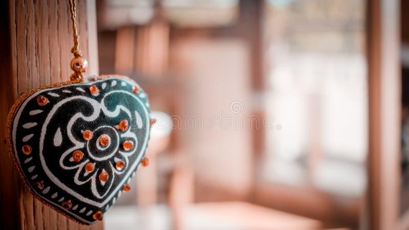 Liebeskonzept mit dem dekorativen Herzhängen und unfocused Haushintergrund lizenzfreie stockfotos