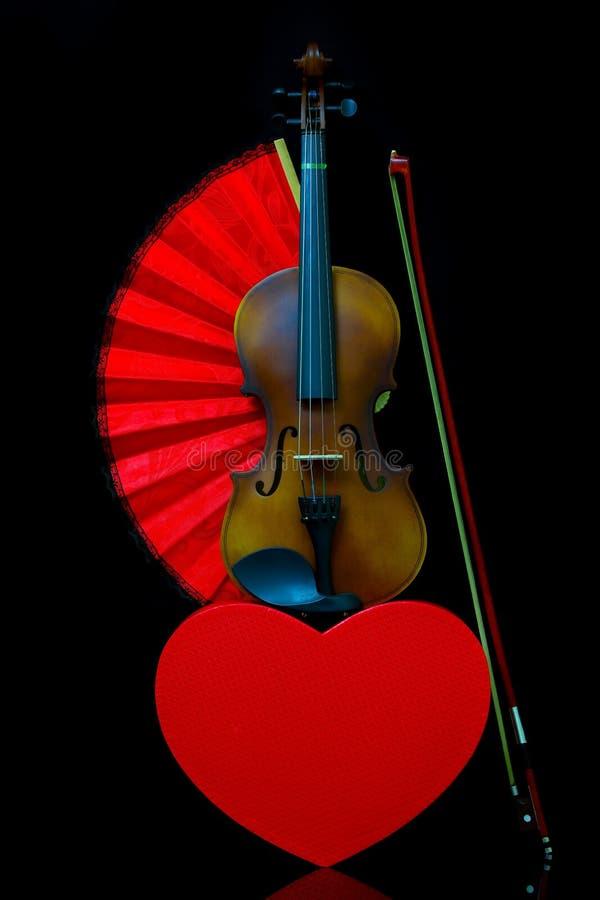 Liebeskonzept mit Geige, Geschenkbox mit Herzform und einem roten Klappventilator stockfotografie
