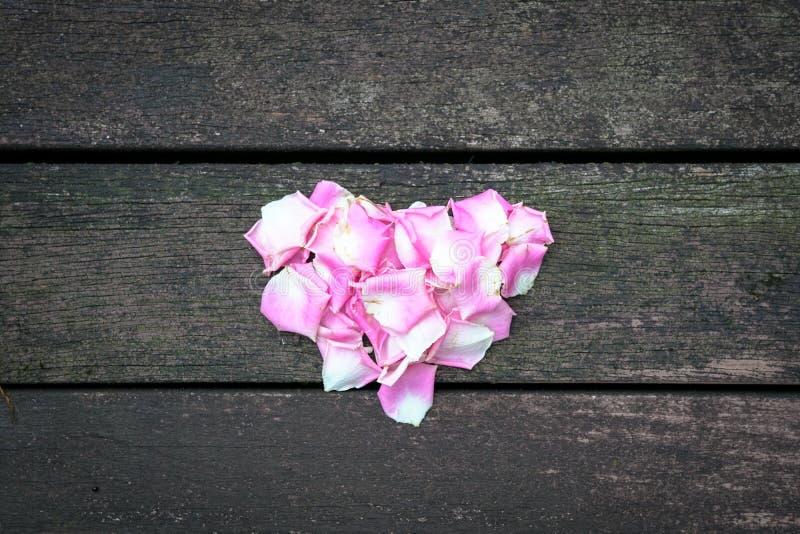 Liebeskonzept: Rosen-Blumenblätter, die eine Herzform in der Mitte eines dunklen hölzernen Hintergrundes bilden lizenzfreies stockbild