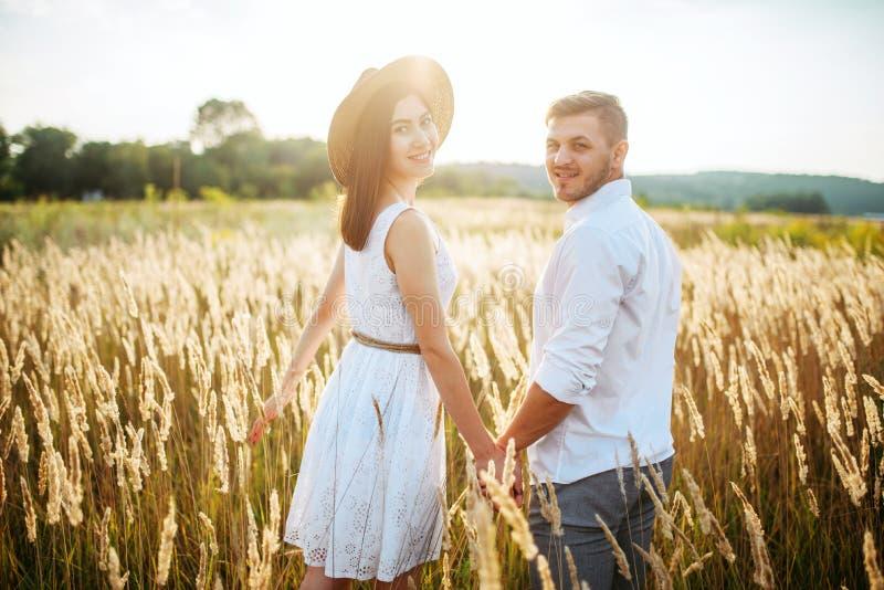 Liebespaare halten die Hände und gehen auf einem Roggengebiet lizenzfreie stockbilder