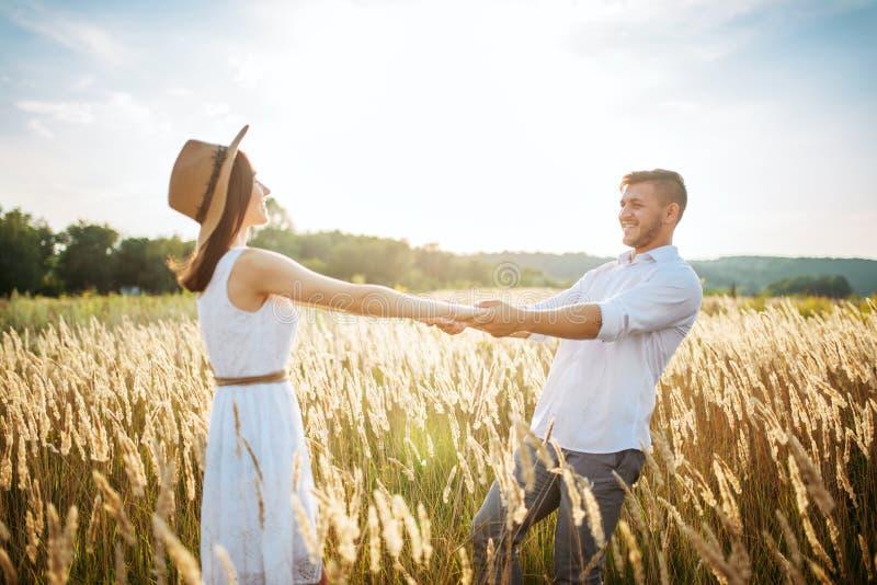 Liebespaare halten die Hände und gehen auf einem Roggengebiet lizenzfreies stockfoto