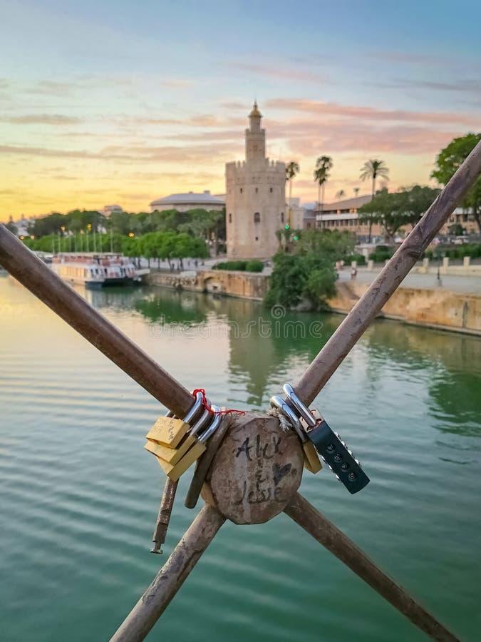 Liebesvorhängeschlösser auf Sevilla-Brücke mit goldenem Tower Torre Del Oro und der Guadalquivir-Fluss im Hintergrund bei Sonnenu stockbild