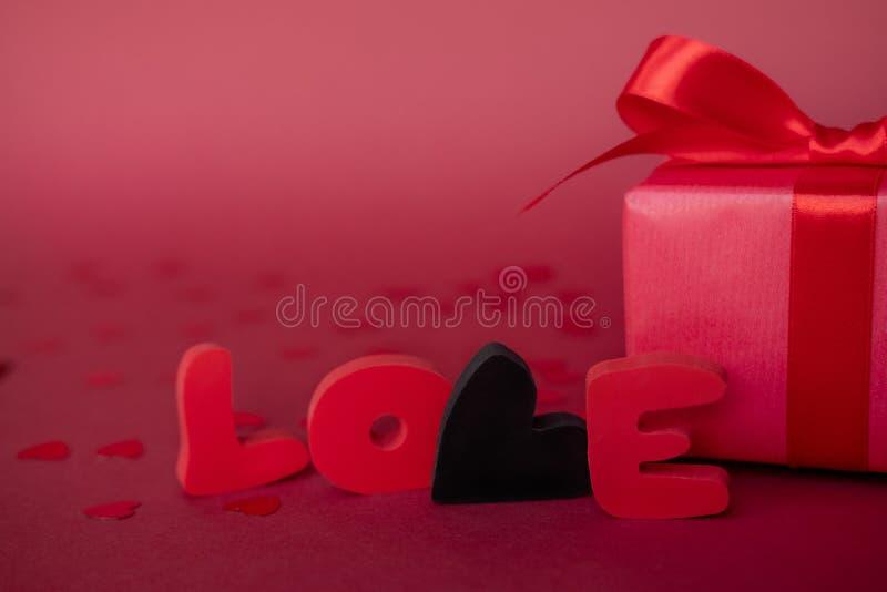 Liebeswort mit roter Geschenkbox auf rotem Hintergrund Bemuttern Sie ` s, Frauen ` s, Hochzeit, glückliches St.-Valentinsgruß-Tag stockfoto