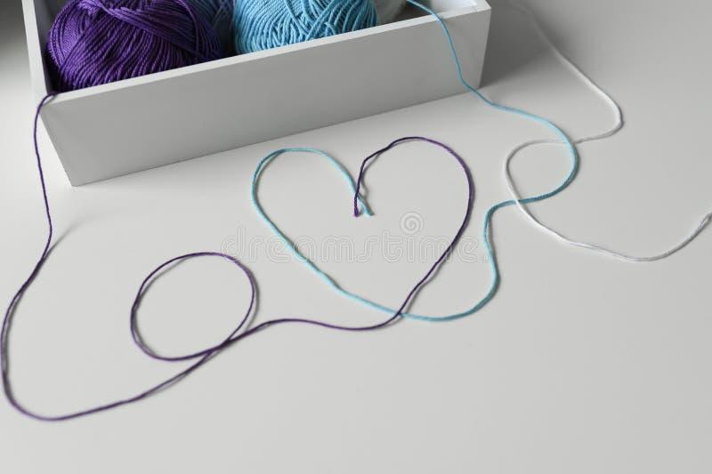 Liebeswort und -herz entworfen von den bunten Wollfaden auf weißer Tabelle von Strickgarn in einem hölzernen Kasten lizenzfreie stockfotos