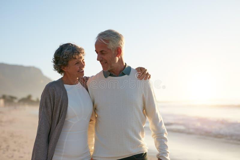 Liebevolle ältere Paare, die einen Weg auf dem Strand haben stockfotos