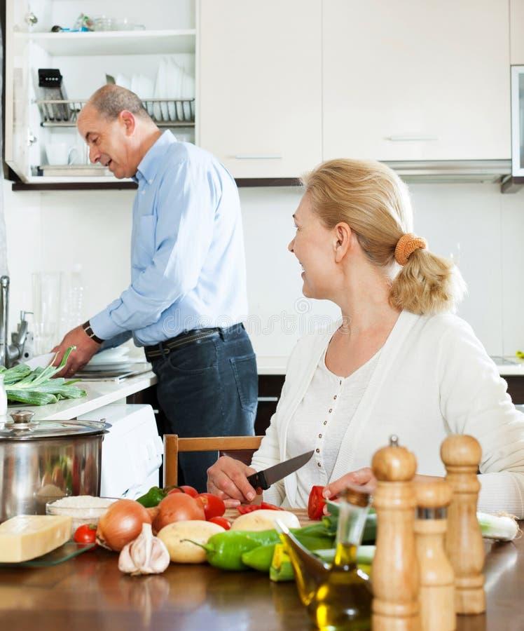 Liebevolle ältere Paare, die Hausarbeit tun und zusammen kochen lizenzfreie stockfotografie